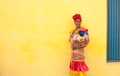 Cuban Woman in Colorful Dress in Front of Yellow Wall